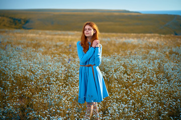 beautiful woman in a blue dress is standing in a field of flowers