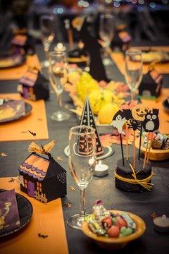 Table de réception avec une nappe noire et des décorations pour les fête d'halloween,une petite maison en carton , des verres et des assiettes en cartons