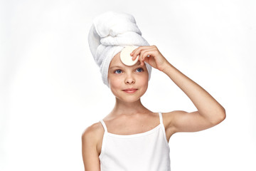 little girl in a towel washing her face