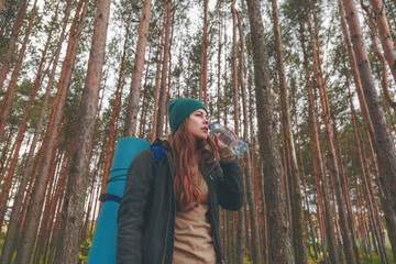 Hiker girl enjoying water. Happy woman tourist with backpack drinking water from bottle in nature.