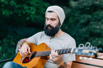 Bearded man in a hat sitting on a bench with a guitar