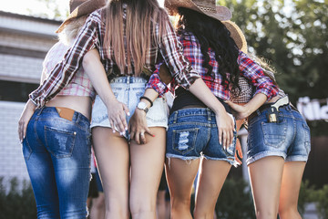 Women are turning to priests in denim shorts young beautiful sensual at the party together in cowboy style