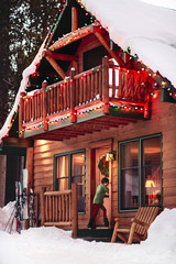 Boy goes in the front door of a cabin decorated with holiday lights at dusk in snow