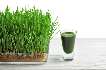 Composition with shot of healthy wheat grass juice on white wooden table