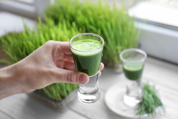 Hand of young man with shot of wheat grass juice