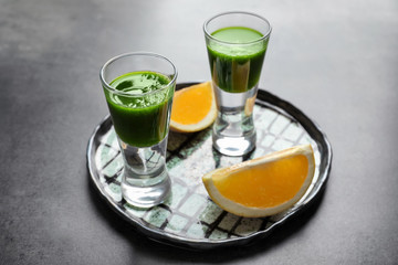 Shots of healthy wheat grass juice on plate