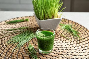 Shot of healthy wheat grass juice on wicker mat