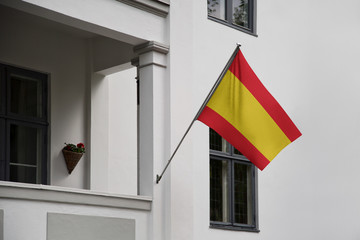 Spain flag. Spanish flag displaying on a pole in front of the house. National flag of Spain Espana waving on a home hanging from a pole on a front door of a building.