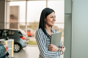 Young car saleswoman holding clipboard in showroom.