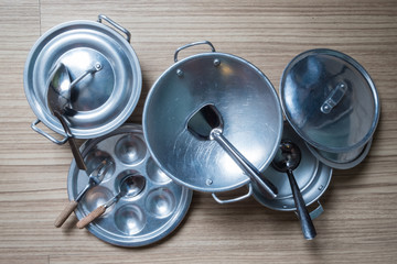 Stainless steel cooking utensils on wooden floor. A toys for children.