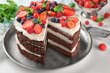 Fototapete - Delicious chocolate cake with berries on table