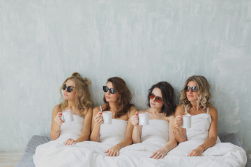 Crazy party time of four beautiful stylish women. group of beautiful young woman napping in her bed after party in sunglasses. Sexy stylish young woman model lying in bed.