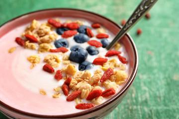 Tasty breakfast with goji berries in bowl on table