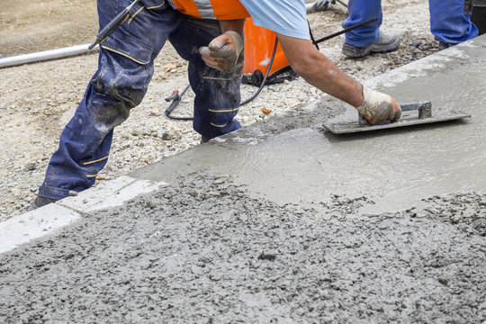 Builder hand leveling concrete with trowel