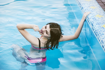 Woman young beautiful brunette in pink bathing suit in the pool