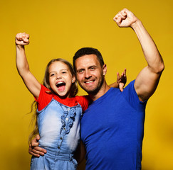 Dad and daughter put their fists up for victory.