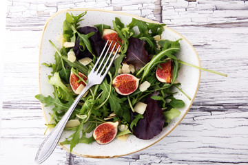Autumn salad of arugula, figs in a white earthenware plate.