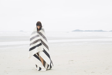 A woman wrapped in a striped blanket standing on a beach
