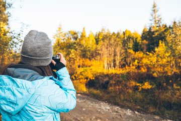 woman taking picture of the autumn carpathian mointains