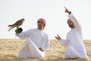 Middle Eastern men hunting with falcon. Dubai. U.A.E