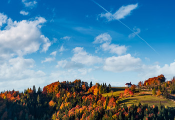 church on a hill under a beautiful cloudy sky. lovely autumn scenery with forest in red foliage