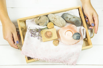 the girl is holding a wooden tray with accessories for spa procedures with a floppy, candles and soap. Flat lay. Top view