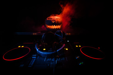 Halloween pumpkin on a dj table with headphones on dark background with copy space. Happy Halloween festival decorations and music concept. Toned