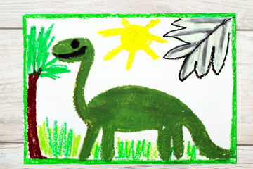 Photo of colorful drawing: Smiling dinosaur. Big green diplodocus