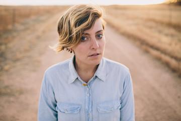 Girl in denim shirt standing on dirt road