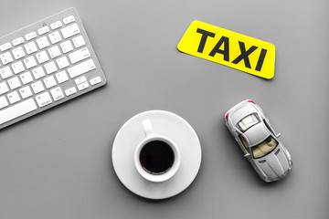 Call taxi online. Taxi label, keyboard, coffee on grey background top view