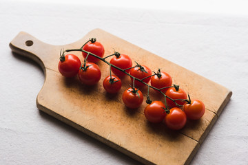 Cherry tomatoes on wooden surface on white background.