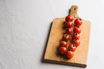 Cherry tomatoes on wooden cutting board against white background.