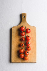 Vertical orientation of cherry tomatoes on wooden board against white background.