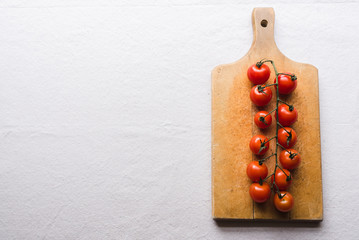 Cherry tomatoes on wooden cutting board on white background.