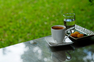 hot black coffee or hot American coffee in white cup Served with Met Khanoon (Golden Jackfruit Seeds Thai Mung Bean Marzipan and Egg Yolk Dessert) green lawn garden.have some space for write wording