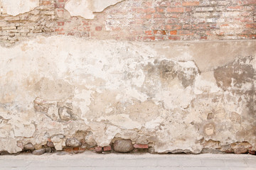 Old weathered vintage brick wall with broken plaster and pavement on the ground. Grungy urban...