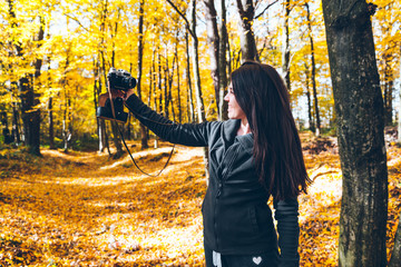 youang pretty woman taking picture in yellow forest