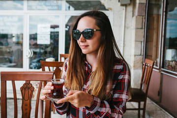 Beautiful young girl with sunglasses on head smiling sitting at table in an outdoor cafe and drinking tea from glass beaker