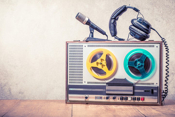 Retro reel to reel tape recorder, microphone and headphones on wooden table front concrete wall background. Vintage style filtered photo