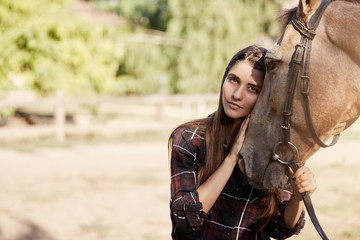 Portrait of young woman and a horse. Longhaired beautiful girl holding and calming down a stallion.