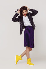 Wall Mural - Young beautiful woman in a black jacket and yellow shoes.