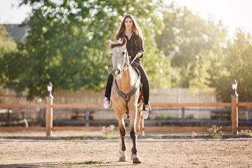 Portrait of young woman riding a horse. Dreaming to become a stallion manager to move from office to farm.
