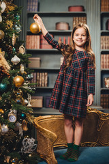 Pretty girl with charming smile stands on armchair, decorates New Year tree alone, has good mood, feels proud to do it by herself. Small kid prepares for Christmas. Childhood and holidays concept