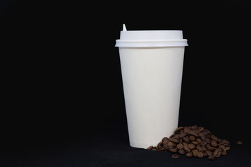 White disposable cup and coffee beans isolated on black