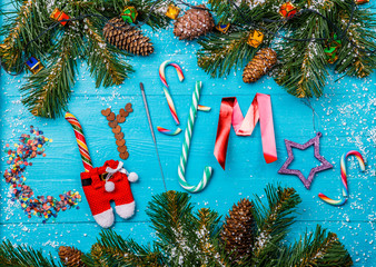 Image of blue table with spruce branches, word Christmas