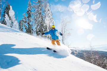 Shot of a male freerider skiing in the mountains on fresh powder snow on a beautiful sunny winter day