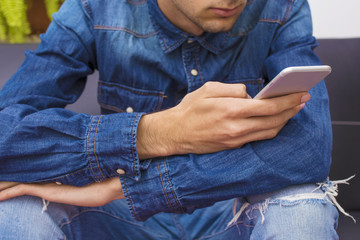 young man sitting on the couch with the mobile phone