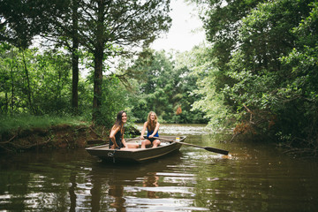 Two young girls explore a beautiful lake by rowboat