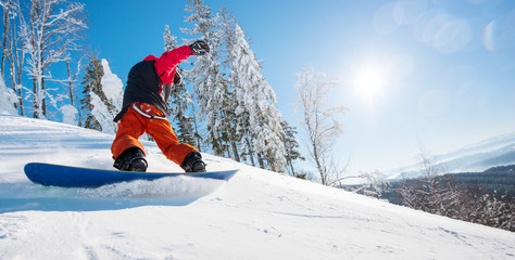 Horizontal low angle shot of a male snowboarder riding the slope on a sunny winter day in the mountains. Forest, blue sky and sun on the background. copyspace freeride snowboarding active lifestyle