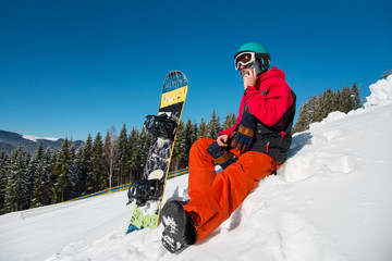 Full length shot of a snowboarder resting sitting on the slope, talking on the phone at ski resort on a beautiful sunny winter day in the mountains